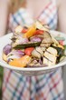 Woman holding a plate of grilled vegetables