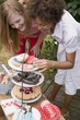 Two women at cake buffet in garden on the 4th of July (USA)