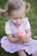 Small girl sitting on grass, holding strawberry ice cream cone