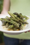 Person holding a plate of grilled green asparagus