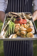 Man holding aluminium tray of grilled vegetables