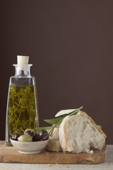 Thyme oil in bottle, olives & white bread on chopping board