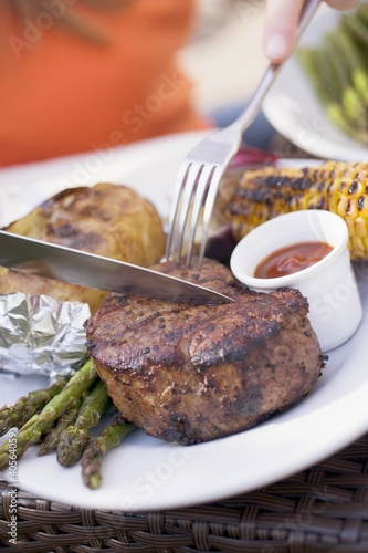 Person eating grilled beef steak