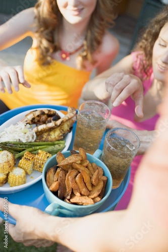 Man serving two women with tray of grilled food & iced tea
