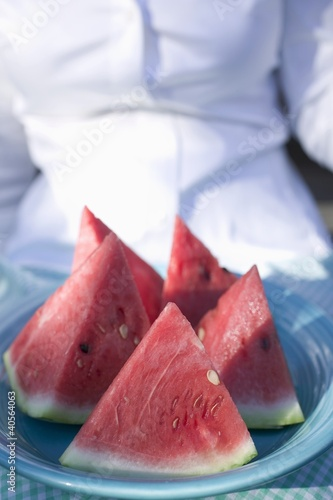 Woman holding a plate of watermelon wedges
