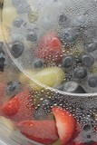 Fruit salad in plastic container (close-up)