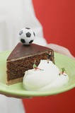 Person holding piece of Sacher torte with cream & football