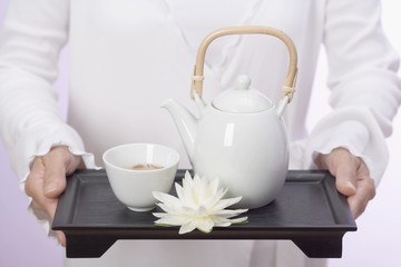 Woman holding teapot, tea bowl and water lily on tray