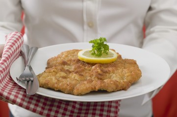 Woman holding plate of Wiener schnitzel (veal escalope)