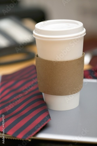 Coffee cup and tie on desk in office
