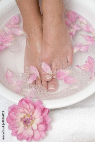 Woman enjoying a soothing foot bath with flower petals