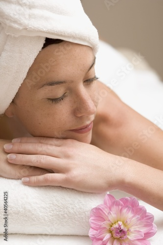 Woman lying down, resting on white towel