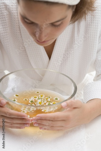Woman bending over bowl of chamomile tea with flowers