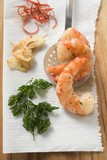 Garlic prawns on slotted spoon, ingredients beside it