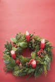 Advent wreath with four burning candles on red background