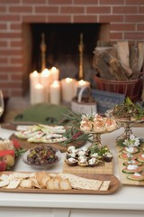 Assorted appetisers on table in front of fireplace (Christmas)