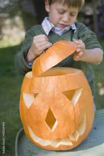 Small boy putting lid on pumpkin lantern