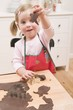 Small girl cutting out chocolate biscuits