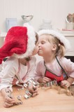 Two small girls in Father Christmas hats kissing in kitchen