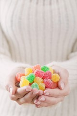 Hands holding coloured sugar-coated jelly sweets