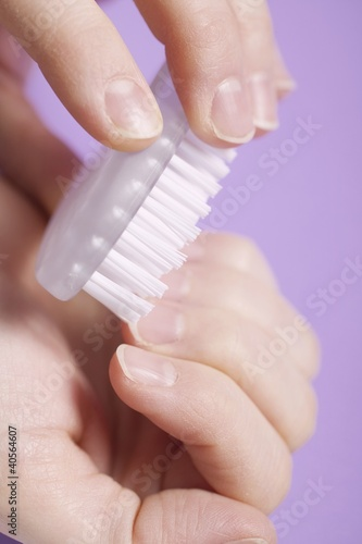 Woman scrubbing her fingernails