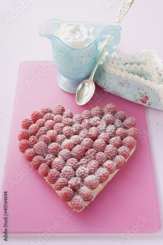 Raspberry tart with icing sugar, whipped cream in small jug