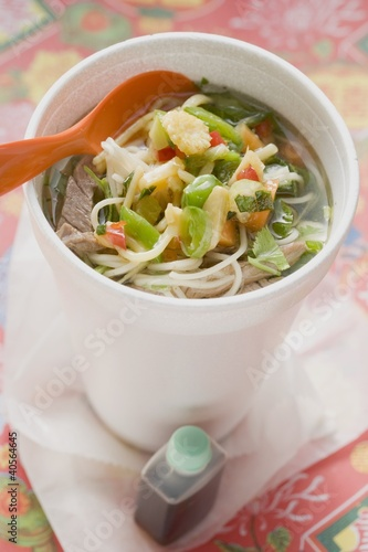 Noodle soup with beef and vegetables in cup, soy sauce