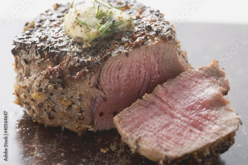 Peppered steak with herb butter, a slice cut off