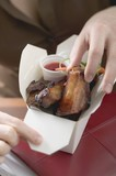 Woman taking glazed pork rib out of take-away container