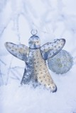 Silver angel and Christmas bauble in snow