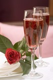 Two glasses of pink champagne, red rose beside them