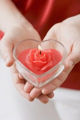 Hands holding heart-shaped windlight with rose candle