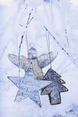 Stars and silver angel on snowy branch