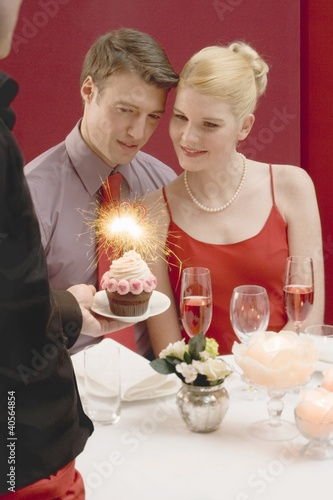 Waiter serving cupcake with sparkler to romantic couple