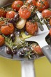 Fried cherry tomatoes with garlic and olives in frying pan