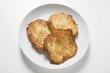 Three potato rostis on plate (overhead view)