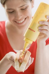 Young woman putting mustard on hot dog