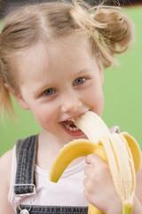 Little girl eating banana