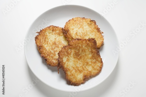 Three potato rostis on plate (overhead view)