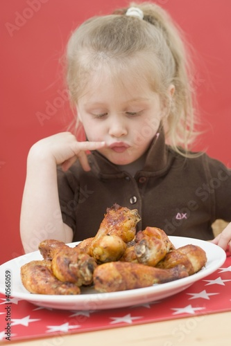 Little girl looking at plate of chicken drumsticks