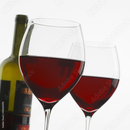 Two glasses of red wine in front of bottle