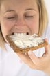 Woman biting into a slice of bread and butter
