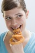 Young woman biting into deep-fried onion ring on index finger