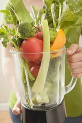 Woman holding fresh vegetables in liquidiser