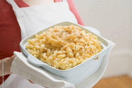 Woman holding baking dish of macaroni cheese