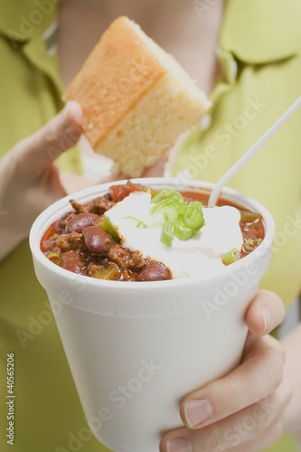 Woman holding chili con carne in paper cup and cornbread