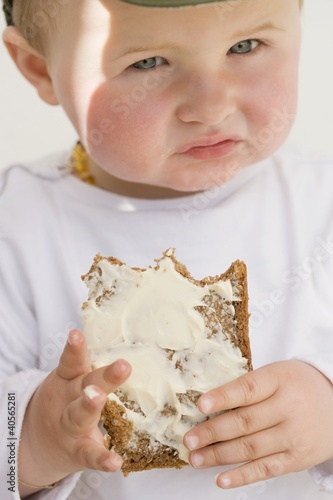 Baby holding a partly-eaten slice of bread and butter
