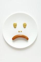Frankfurter and mustard making a sad face
