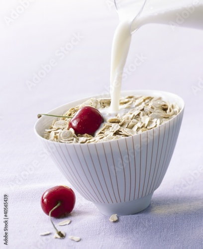 Pouring milk onto oat flakes