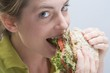 Woman biting into a sandwich with enjoyment